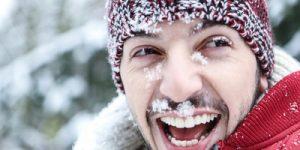 Lachender Mann mit Schnee im Gesicht im Winter