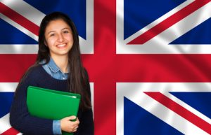 Teen student smiling over English flag. Concept of lessons and learning of foreign languages.