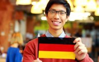 Happy asian student holding flag of germany